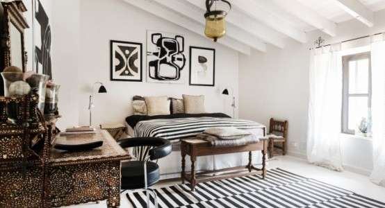 Luxury-Country-House-With-An-Eclectic-Interior-with-white-black-bed-pillow-blanket-nighstand-chandelier-dresser-mirror-window-curtain-carpet-and-wooden-ceiling-and-ceramic-floor-554x300
