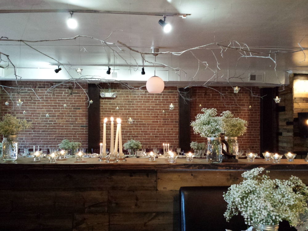spray painted branches hanging from ceiling with floating tealights