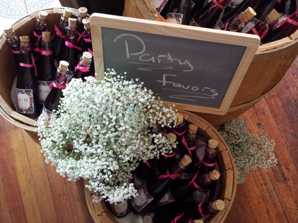 Mini wine bottle party favors in rustic barn barrels